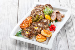 Juicy delicious meat cutlets and homemade sausage with pickled vegetables on plate on wooden background Royalty Free Stock Photo