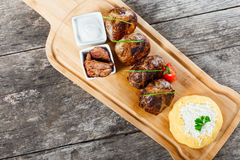 Juicy delicious meat cutlets and hominy or Corn porridge Polenta with goat cheese on cutting board on wooden background Stock Photography