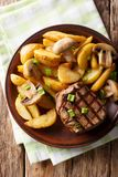 Juicy fillet mignon with fried potato wedges and mushrooms close. Up on a plate on a table. Vertical top view from above Stock Images