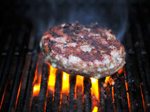 Juicy Flame Broiled Bleu Cheese Hamburger Grilling. A juicy flame broiled bleu cheese burger cooking on the charcoal grill for dinner.  The burger is smoking and Stock Images