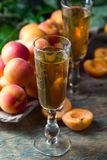Juicy fresh apricots and glass of sweet liquor. Juicy fresh apricots and glass of sweet liquor on old wooden table Stock Images