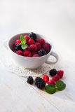 Juicy fresh blueberries, raspberries and blackberries in a white plate. On old wooden background, selective focus Royalty Free Stock Image