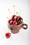 Juicy fresh cherries in brown cup Royalty Free Stock Images