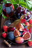 Juicy fresh fruits  and wine glass on dark wooden background Royalty Free Stock Photography