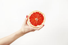 Juicy fresh grapefruit in a beautiful woman`s hand  on white. Royalty Free Stock Images