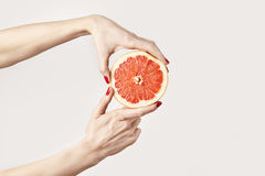 Juicy fresh grapefruit in a beautiful woman`s hands  on white. Royalty Free Stock Photography