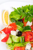 Juicy fresh Greek salad in white bowl. On a white background, close-up Royalty Free Stock Photo