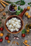 Juicy fresh mozzarella cheese in a bowl. A bowl of olives served Royalty Free Stock Photography