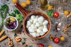 Juicy fresh mozzarella cheese in a bowl. A bowl of olives served Stock Photos