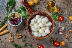 Juicy fresh mozzarella cheese in a bowl. A bowl of olives served Royalty Free Stock Photo