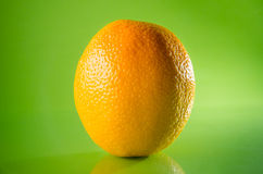 Juicy fresh orange isolated on green background, horizontal shot. Picture presents juicy fresh orange isolated on green background, horizontal shot Royalty Free Stock Photography