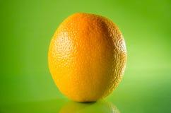 Juicy fresh orange isolated on green background, horizontal shot Royalty Free Stock Photography