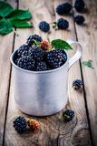 Juicy fresh organic blackberries in old mug. On a wooden background Stock Photo