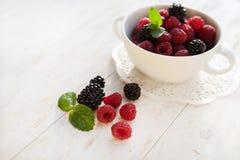 Juicy fresh  raspberries and blackberries. In a white plate Royalty Free Stock Photo