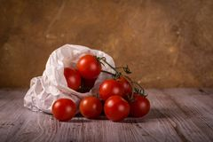 Juicy fresh red tomatoes on wooden board in paper bag. Horizontal photo with few twigs full of small red cherry tomatoes. Vegetable is placed in worn crumpled royalty free stock photo