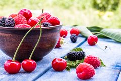 Juicy fresh tasty berries raspberries, cherries, mulberries in a bowl on blue boards on a background of green grass. Close-up royalty free stock images