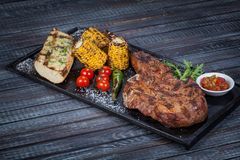 Juicy, fried, tender steak with vegetables and sauces on a special stand stock photos