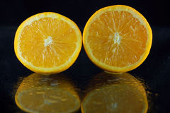Juicy Fruit. An orange which has been cut in half, sits on a black surface.  The reflection of the oranges is seen in the surface.  There are water drops on the Stock Photo