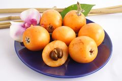 Juicy fruit. Blue plate with some fresh colorful loquats royalty free stock photography