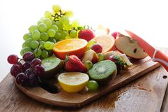 Juicy fruits with knife on a wooden board Royalty Free Stock Photos