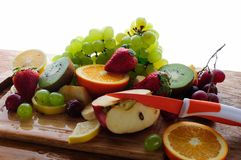 Juicy fruits with knife on a wooden board Stock Image