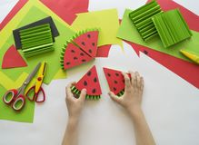 Children`s hands make fruit from paper. Tropics summer. Master class from the child. Stock Photos