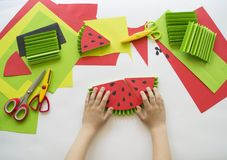 Children`s hands make fruit from paper. Tropics summer. Master class from the child. Stock Images
