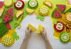Children`s hands make fruit from paper. Tropics summer. Master class from the child. Royalty Free Stock Photography