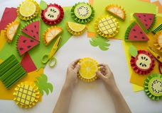 Children`s hands make fruit from paper. Tropics summer. Master class from the child. Stock Image