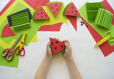 Children`s hands make fruit from paper. Tropics summer. Master class from the child. Stock Photography