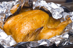 Juicy golden chicken in foil Stock Photos