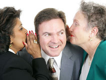 Juicy Gossip at Work. Closeup of a man listening to gossip from two female coworkers. Isolated on white stock photo