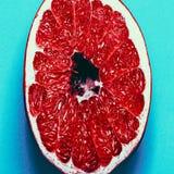 Juicy grapefruit on blue background. Royalty Free Stock Photos