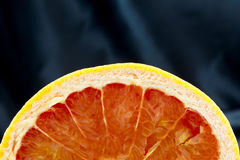 Juicy grapefruit cut in half with black satin background Stock Photo