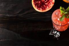 Juicy grapefruit drink on dark table Royalty Free Stock Images