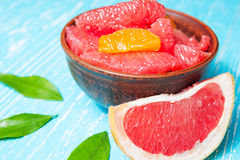 Juicy grapefruit pieces in a bowl, close up. Juicy grapefruit pieces on blue wooden table in a bowl close up royalty free stock photo