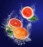 Juicy grapefruit in water splahes Royalty Free Stock Photos