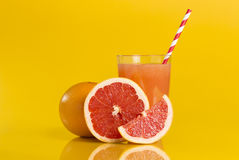 Juicy grapefruit. Whole red grapefruit, cross section and a slice placed next to a glass of grapefruit juice with drinking straw isolated on orange background Royalty Free Stock Photos