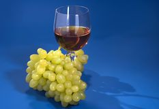 Fresh grapes and glass of wine on a blue background royalty free stock photos