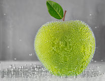 Juicy green apple in the water with bubbles of gas Stock Photos