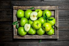 Juicy green apples and Apple slices in a wooden box. On a dark wooden background royalty free stock image