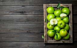Juicy green apples and Apple slices in a wooden box. On a dark wooden background royalty free stock photos