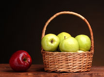 Juicy green apples in basket and red apple. On wooden table on brown background Royalty Free Stock Photo