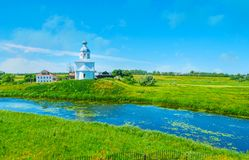 Green banks of Kamenka river, Suzdal. The juicy green banks of Kamenka river with the white church of Ilya the Prophet on the small hill, Suzdal, Russia Stock Images