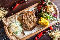 Juicy grilled beef steak on a wooden board with corn, onion and pepper from the top royalty free stock photos