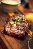 Juicy grilled beef steak on a wooden plate Stock Photography