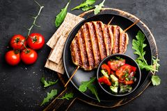 Juicy grilled chicken meat lula kebab on skewers with fresh vegetable salad on black background. Top view royalty free stock photos