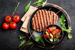 Juicy grilled chicken meat lula kebab on skewers with fresh vegetable salad on black background royalty free stock photos