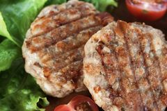 Juicy grilled meat patties with vegetables on a plate royalty free stock photography