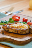 Juicy grilled pork chop (neck cut) on cutting board. Royalty Free Stock Photography